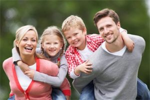 wife and husband with two young kids on their backs smiling