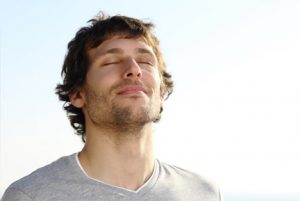 man with stubble taking deep breath of fresh air outdoors