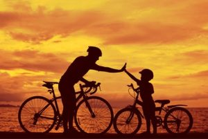 father and child riding bicycles in the sunset