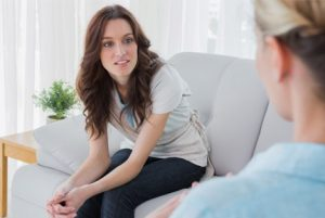 woman sitting on couch, view over therapist's shoulder